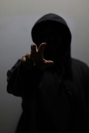 Close-up of man in hooded clothing gesturing against wall li