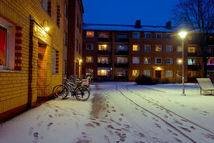 Bicycle parked on snow covered street against buildings at night