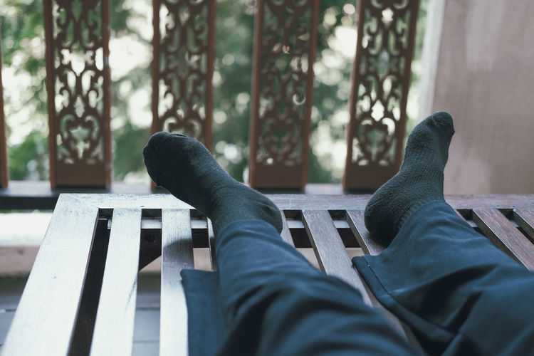 Low section of man resting on bench
