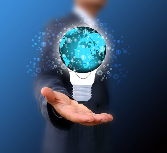 Digital composite image of businessman holding light bulb icon against blue background