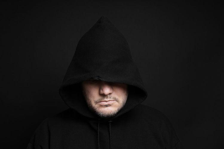 Man Wearing Hooded Shirt Against Black Background