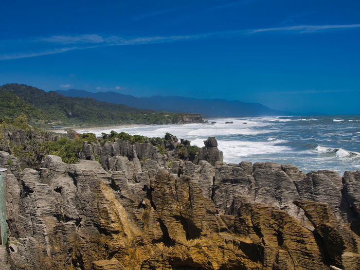 View of the west coast of the South Island from Pancake Rocks, Paparoa National Park, New Zealand Punakaiki New Zealand Landscape Beach Beauty In Nature Blue Cliff Day Mountain Nature No People Outdoors Pacific Ocean Rock - Object Rock Formation Scenics Sea Sky Water EyeEmNewHere EyeEmNewHere