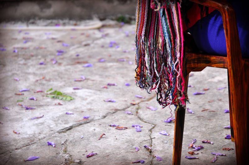 Close-up of tassels from scarf of person sitting on chair