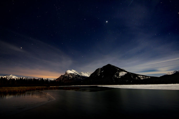 Scenic view of lake and rocky mountains against sky at night