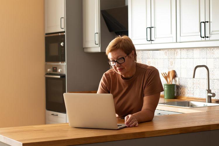 Full length of man using laptop at home