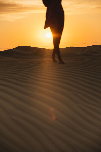 Sunset Orange Color Sky One Person Land Real People Silhouette Nature Sand Walking Standing Human Leg Women Human Body Part Desert Sand Dunes Silhouette