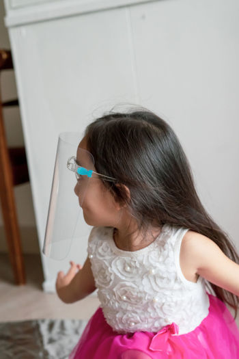 Cute girl wearing face shield at home