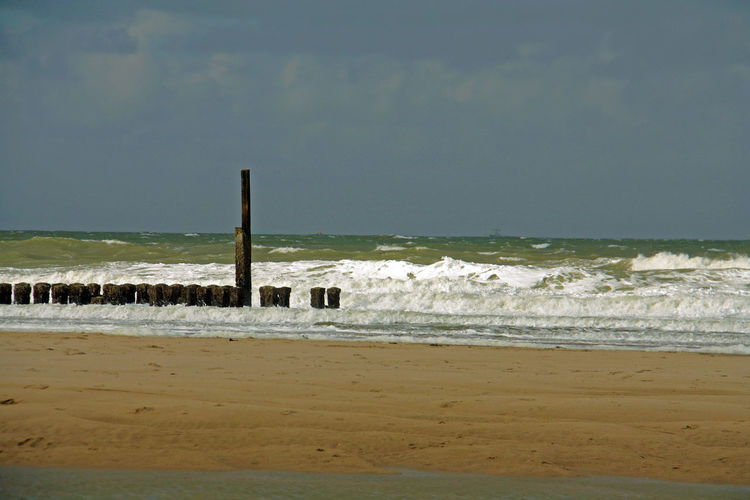 Wooden posts on shore against sky at domburg