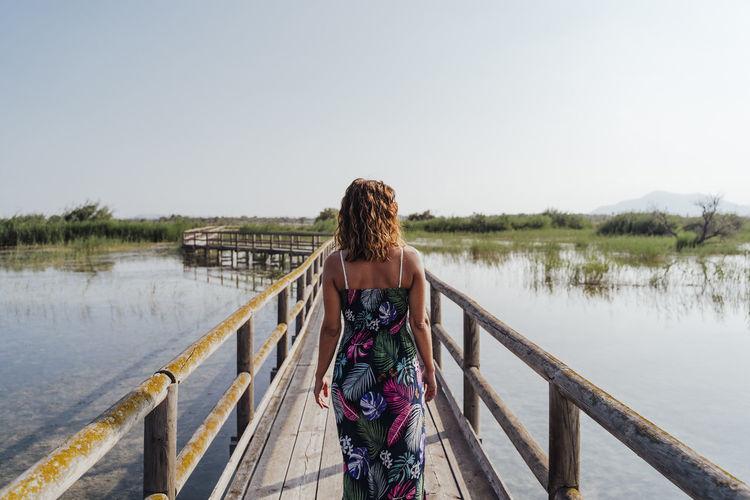 Woman standing on footbridge over lake