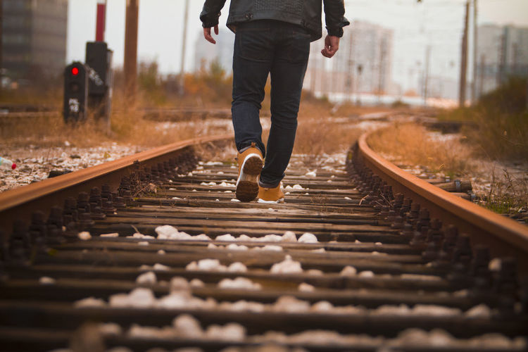 Low Section Of Man Walking On Railroad Track