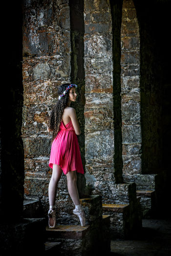 Ballet dancer standing on retaining wall in old building