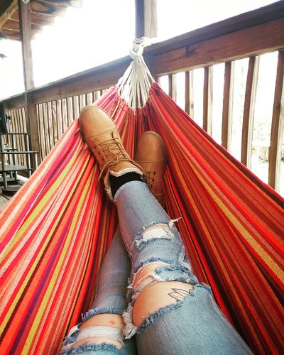 Low section of woman relaxing in hammock