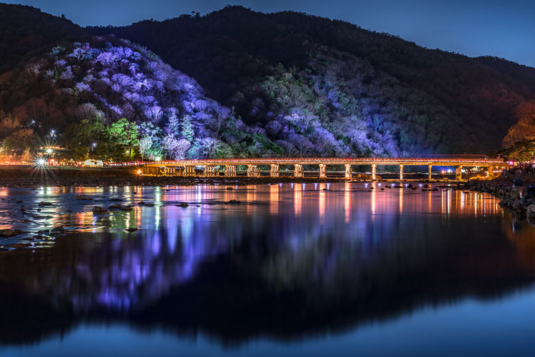 Bridge over river against mountains at night