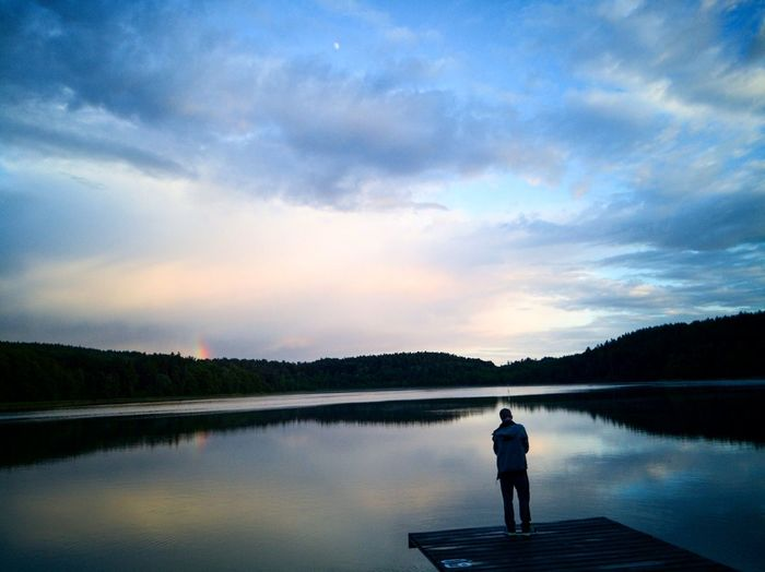 Man standing on pier over lake against sky during sunset