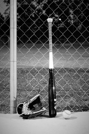Baseball Baseball Bat Baseball Game Baseball Glove Chainlink Fence Close-up Day Fence Focus On Foreground Forbidden Metallic No People Outdoors Part Of Pole Protection Safety Security Monochrome Photography