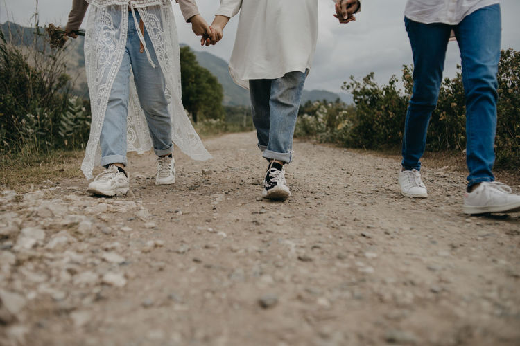 Low section of friends holding hands while walking on dirt road
