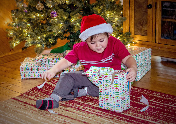 Boy unwrapping gift box while sitting by christmas tree at home