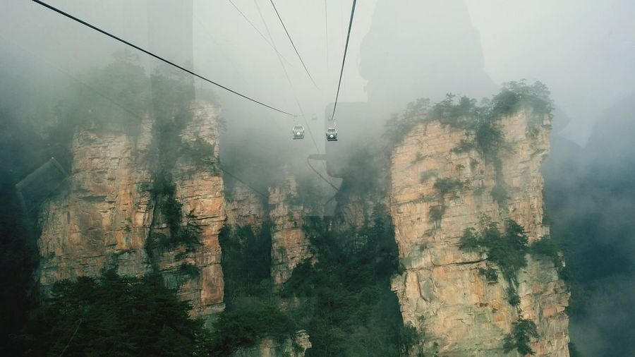 Overhead cable cars amidst rocky mountains during foggy weather