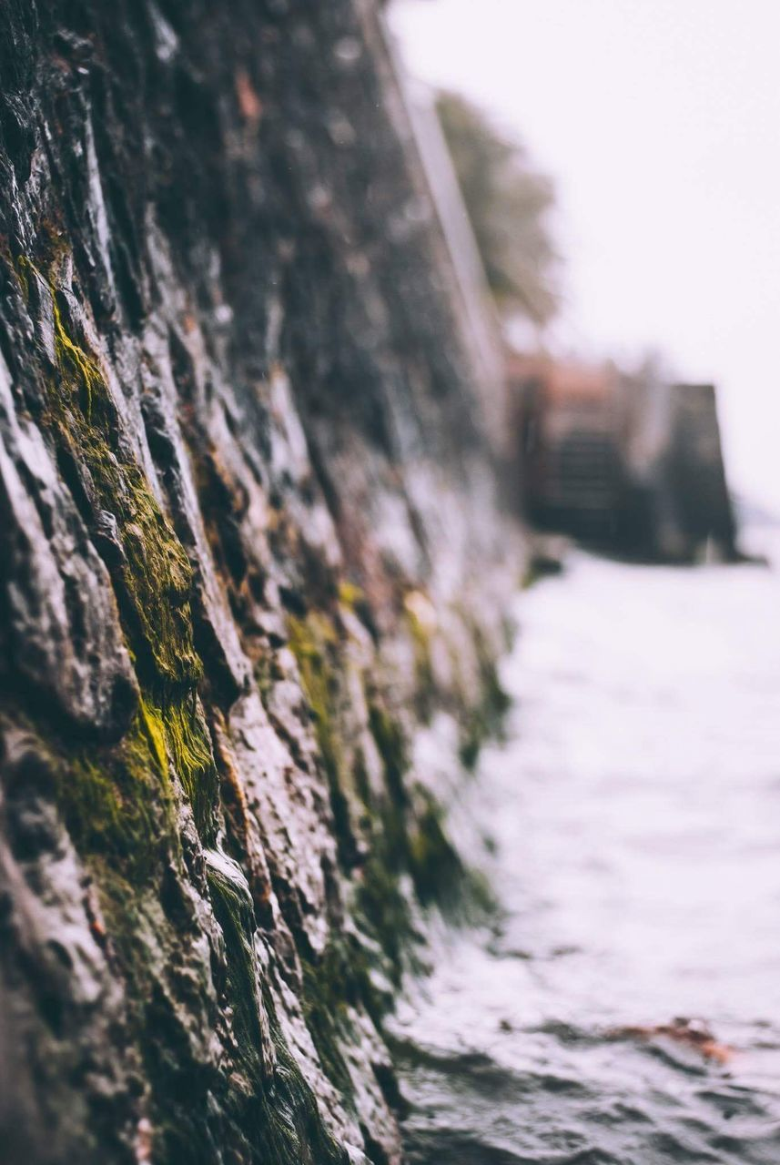 no people, architecture, selective focus, day, built structure, textured, nature, close-up, wall - building feature, outdoors, rough, wood - material, water, tree, building exterior, moss, focus on foreground, waterfront, rock, weathered, stone wall, surface level