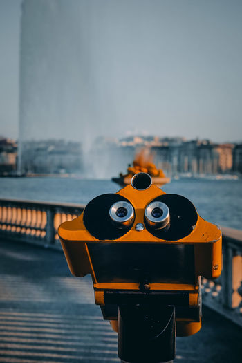 Close-up of coin-operated binoculars on pier against sky. fountain of geneva in the background.