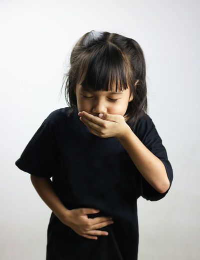 Girl vomiting while standing against white background