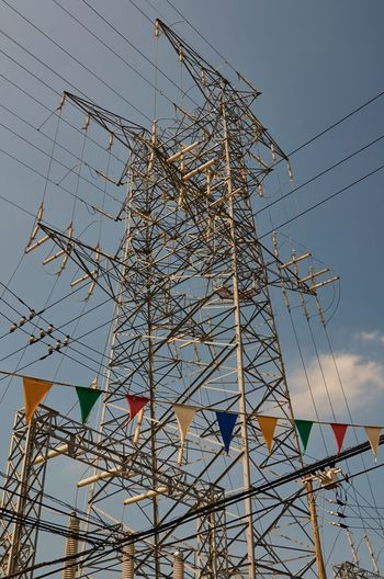 Low angle view of colorful bunting by electricity pylon