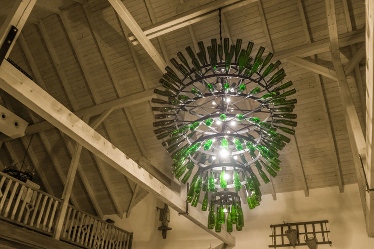 Architectural Design Architecture Art Built Structure Ceiling Day Green Wine Bottles Illuminated In A Barn Indoors  Low Angle View Luster Luster From Wine Bottles No People Rustic Style Wine Bottles