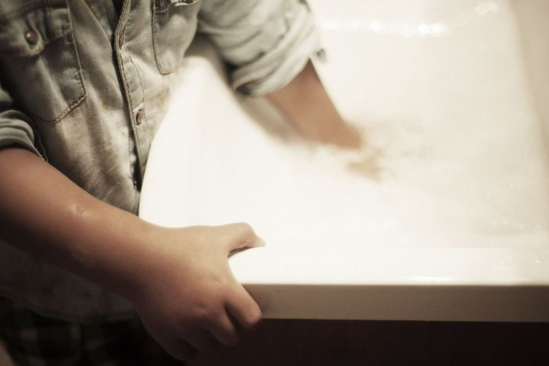 Midsection of boy standing by sink in bathroom