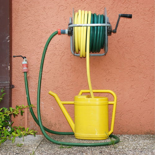 Building Exterior Day Garden Gardening Gardening Tools Green Water Hose No People Orange Color Outdoors Still Life Summer Symbol To Water Tube Water Hose Watering Can Yellow Yellow Color Yellow Watering Can