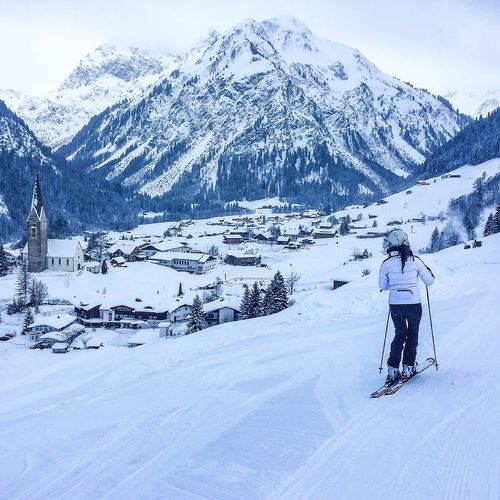 Rear View Of Woman Skiing On Snowcapped Mountain