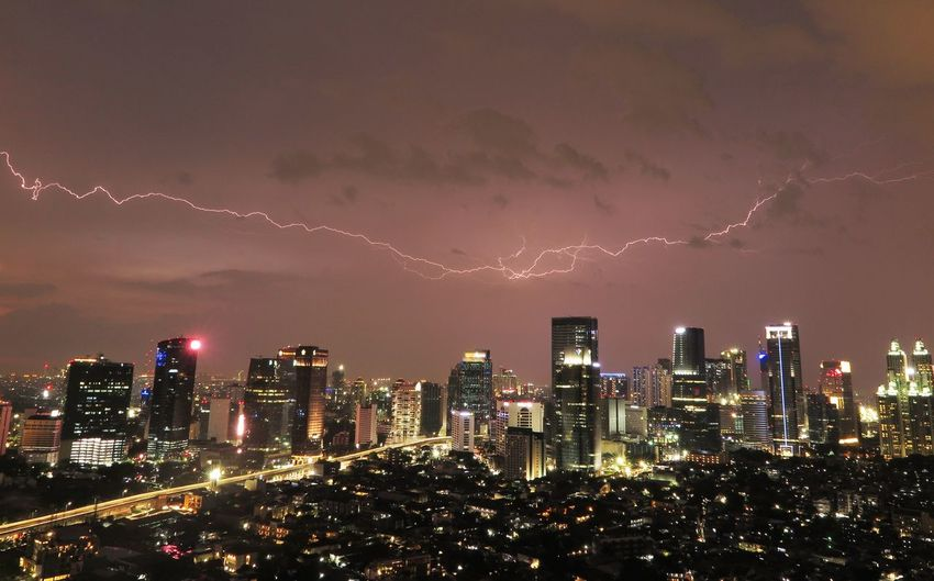 View Of Lightning Over Illuminated City At Dusk