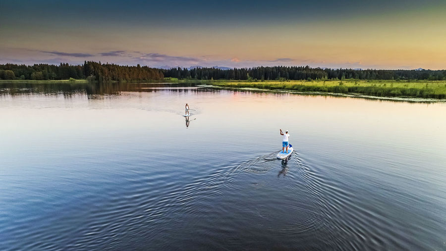 High angle view of friends paddleboarding in lake during sunset