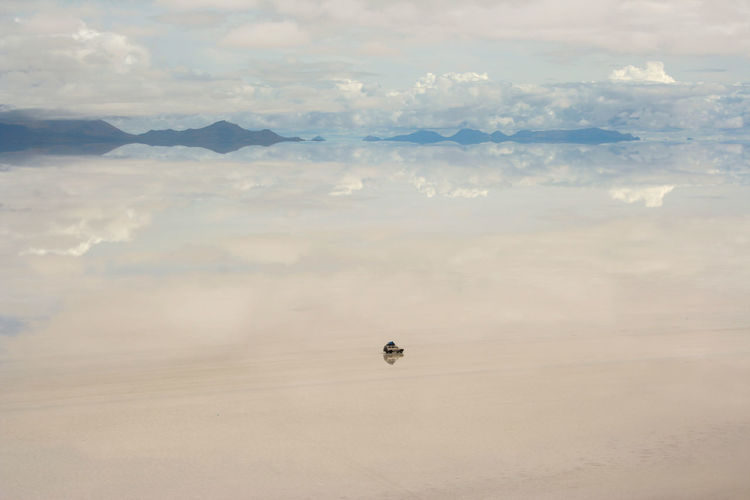 Vehicle With Reflection Of Clouds And Mountains At Salar De Uyuni