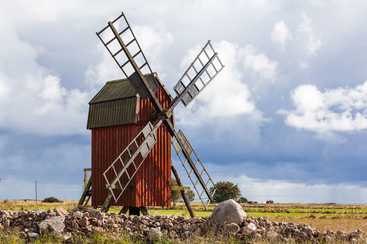 Traditional Windmill On Field Against Cloudy Sky