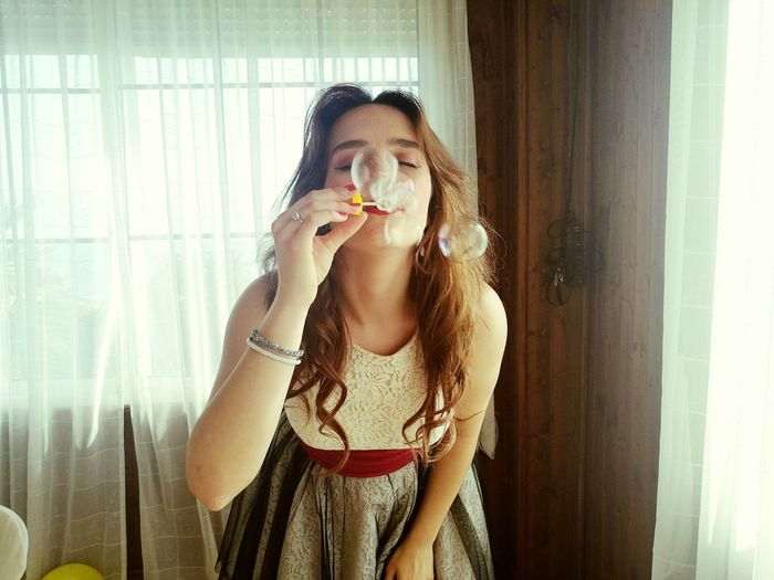 Beautiful woman blowing bubbles at home