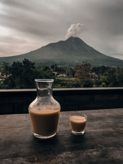 Coffee on table by mountains against sky
