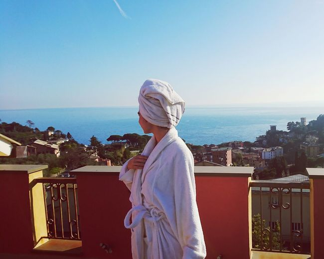 Side view of woman wearing bathrobe while looking at sea on balcony
