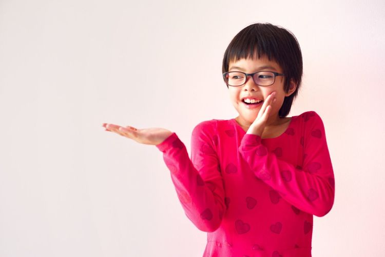 Portrait Asian young girl looking at her empty palm with surprised face and pastel pink wall for advertising Girl Cheerful Pretty Portrait Studio Shot Happiness Smiling Portrait Emotion Cheerful One Person Looking At Camera Gesturing Glasses Positive Emotion Eyeglasses  Indoors  Casual Clothing