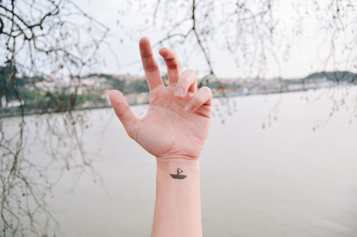 Boat Tattoo Adult Beauty In Nature Close-up Day Focus On Foreground Gesturing Human Body Part Human Finger Human Hand Ink Leisure Activity Lifestyles Nature One Person Outdoors People Real People River Showing Sky Tattoo Tattoos