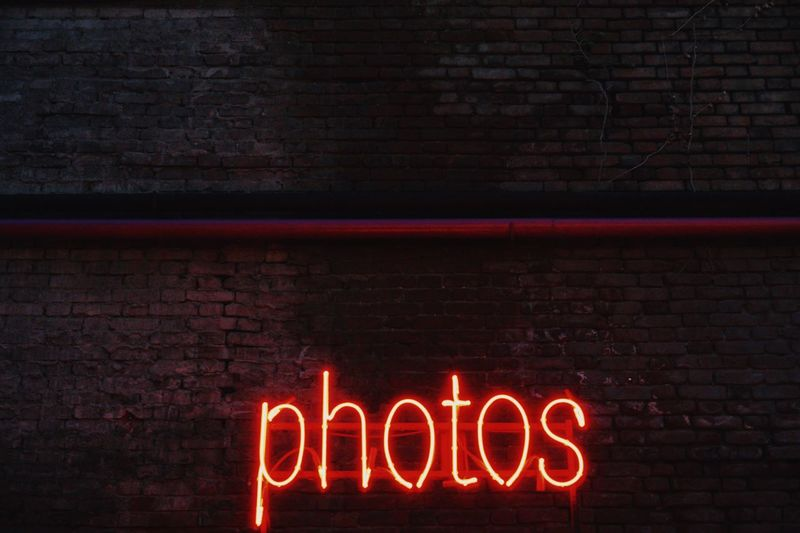 Illuminated neon photos text on brick wall