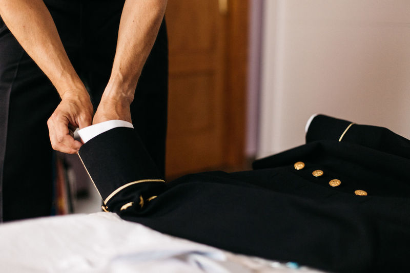 Cropped hand of man adjusting suit at home