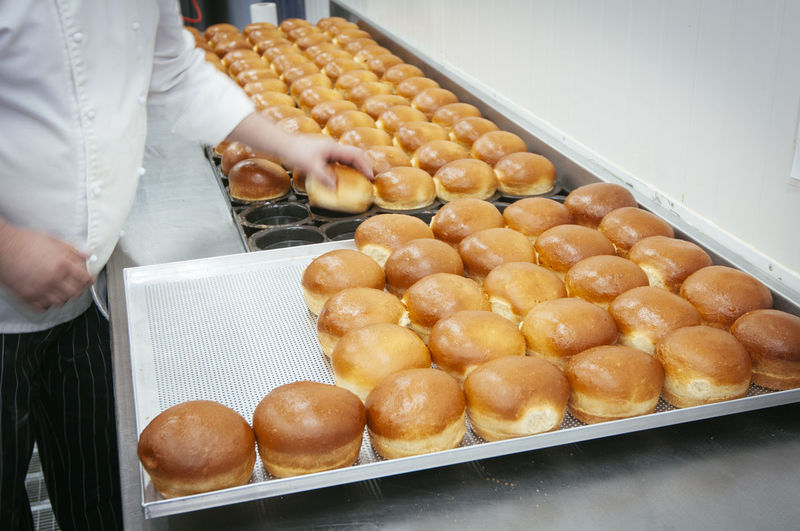 Midsection Of Man Arranging Sweet Buns On Tray In Kitchen