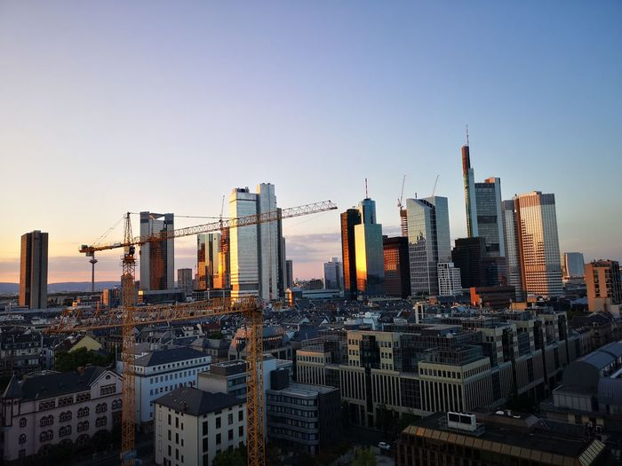 Modern buildings in city against clear sky during sunset