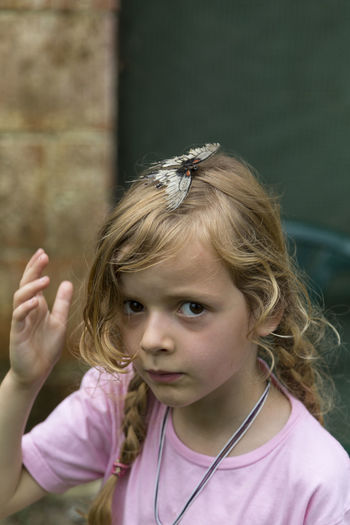 Portrait Of Cute Girl With Butterfly In Hair Outdoors