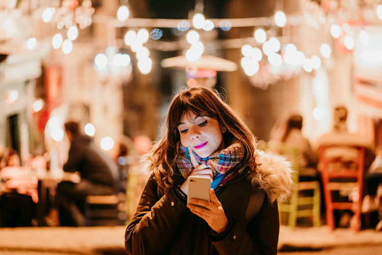 Portrait of smiling young woman holding illuminated outdoors