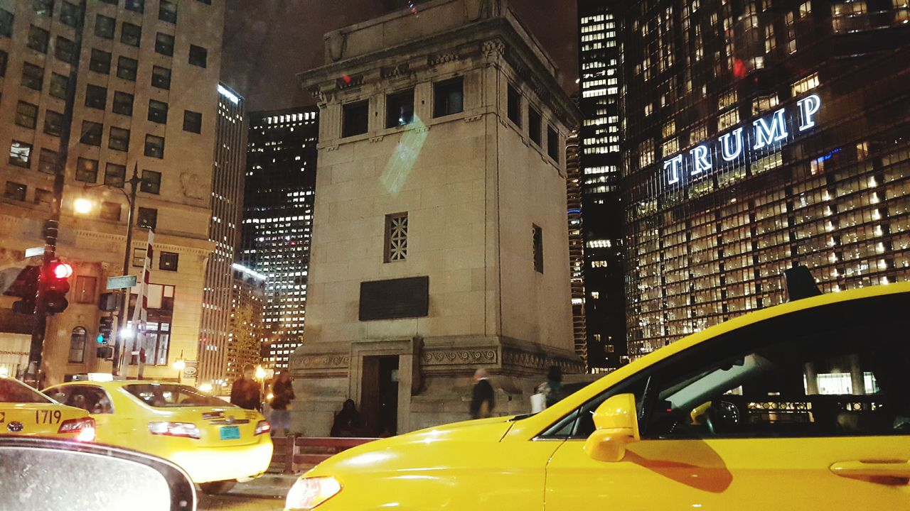 architecture, building exterior, car, built structure, city, illuminated, transportation, night, yellow, land vehicle, skyscraper, no people, outdoors, yellow taxi, cityscape