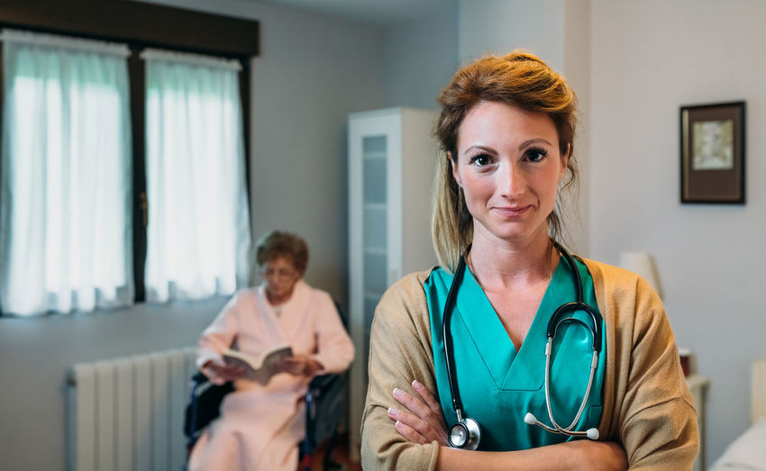 Portrait of confident doctor with arms crossed standing with patient in background