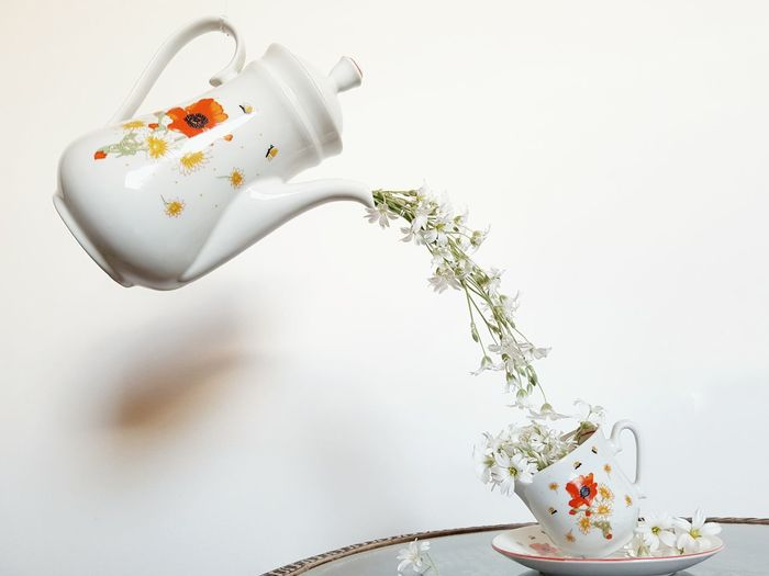 Close-up Of Tea Pot Pouring Flowers In Cup Against White Wall
