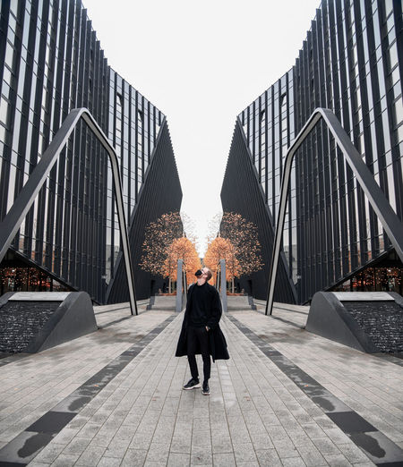 Rear view of man standing on bridge against sky in city