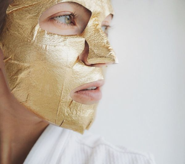 Close-up of woman with golden facial mask over white background